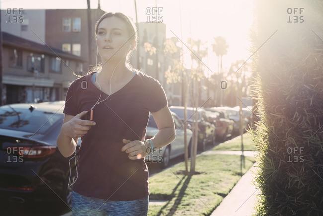 Young woman jogging on a suburban sidewalk