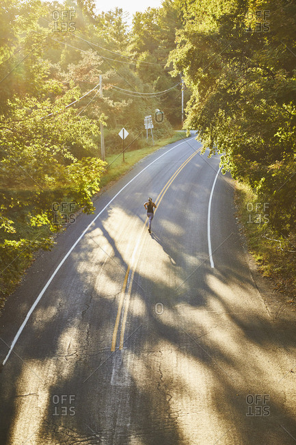 Woman running on an empty rural road