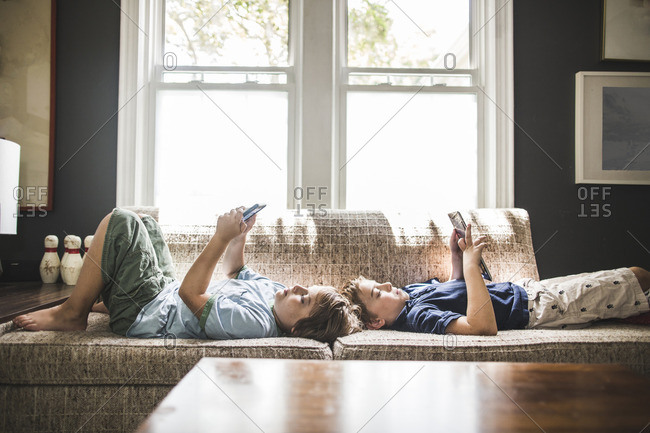 Brothers lying on sofa looking at smart phone and tablet computer