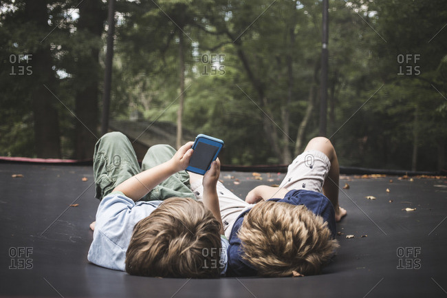 Two boys lying on a trampoline looking at a smart phone