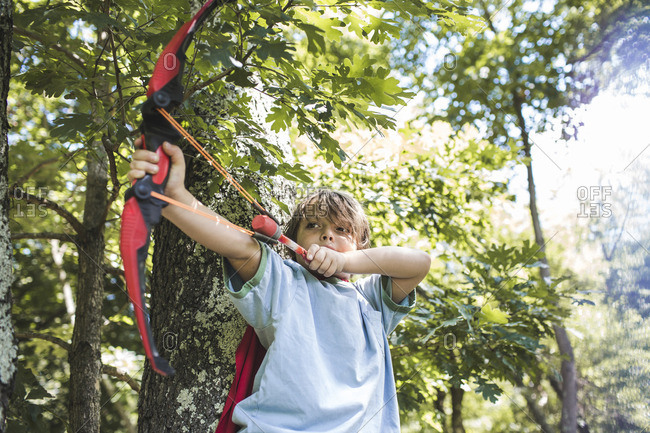 Young boy wearing a red cape shooting a toy arrow
