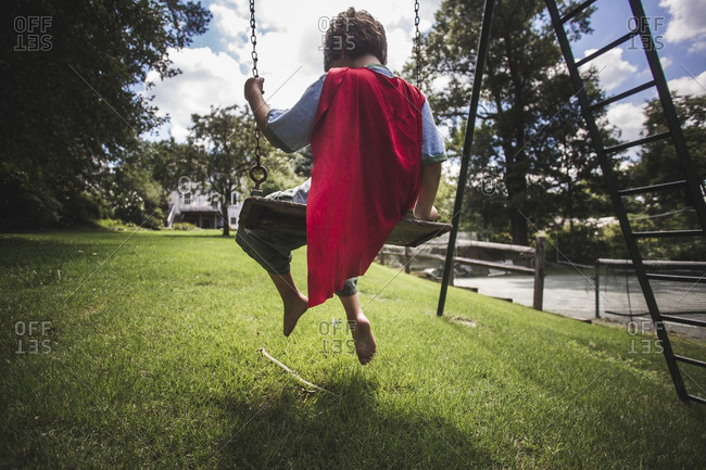 Rear view of boy wearing a red cape sitting on a swing
