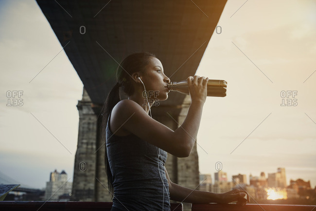 Woman drinking water during workout under a bridge