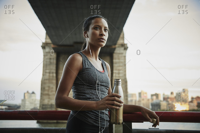 Woman drinking water during workout under the Brooklyn bridge