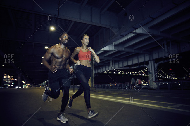 Couple jogging under city bridge