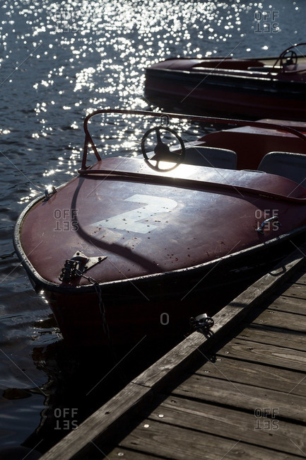 Boat chained to a wooden dock on a sunny day