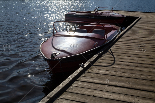 Two boats chained to a wooden dock on a sunny day