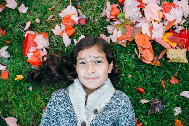 Girl in sweater lying among fall leaves