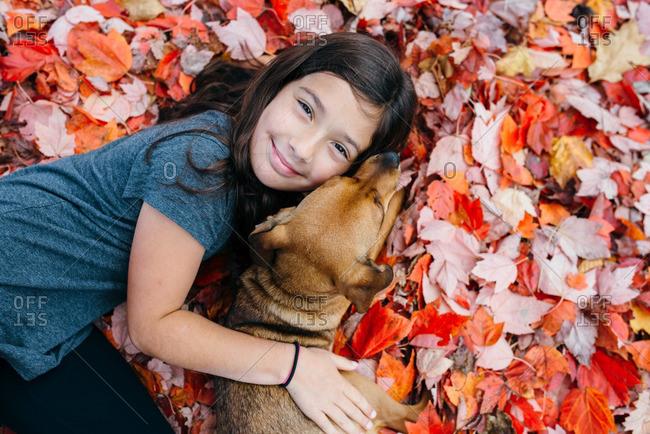 Girl hugging dog in fall leaves