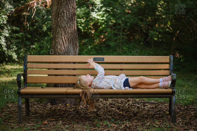 Girl lying on bench in wooded setting
