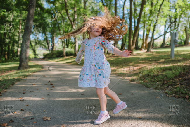 Girl spinning on wooded trail