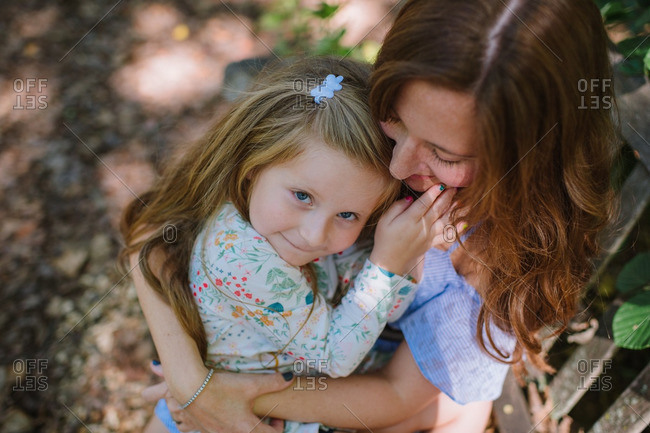 Girl in mom's arms in wooded setting