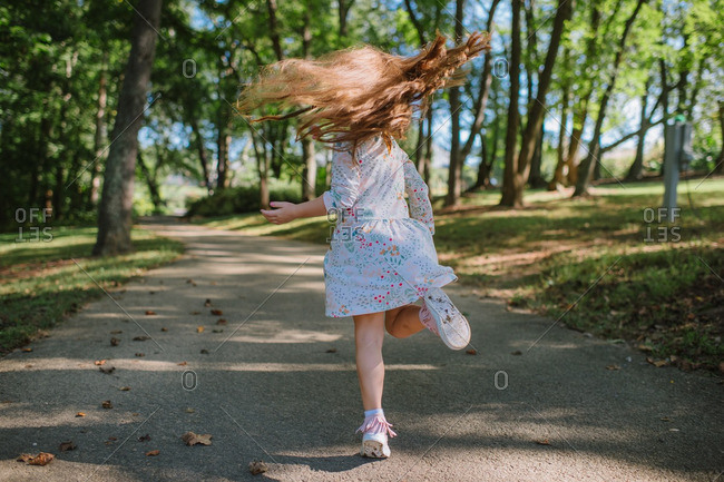 Girl twirling on wooded trail