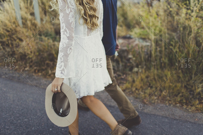 Woman in a white dress holding a cowboy hat walking next to her partner