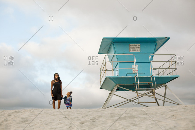 Mom holding her daughter's hand on beach