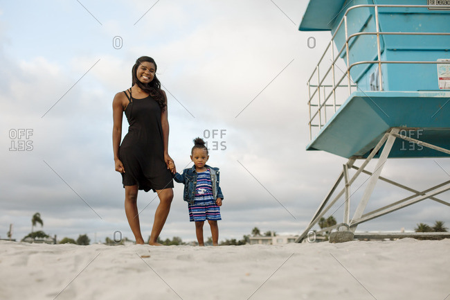 Smiling mom and daughter on beach