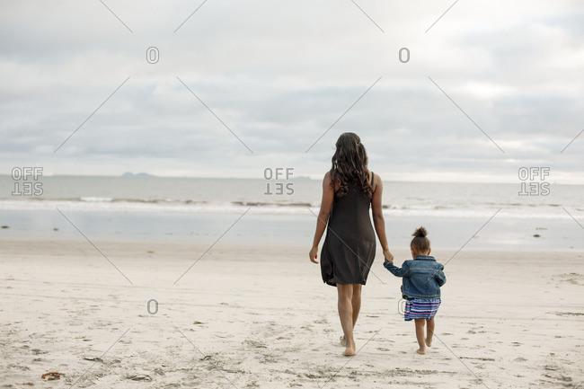Woman exploring beach with girl