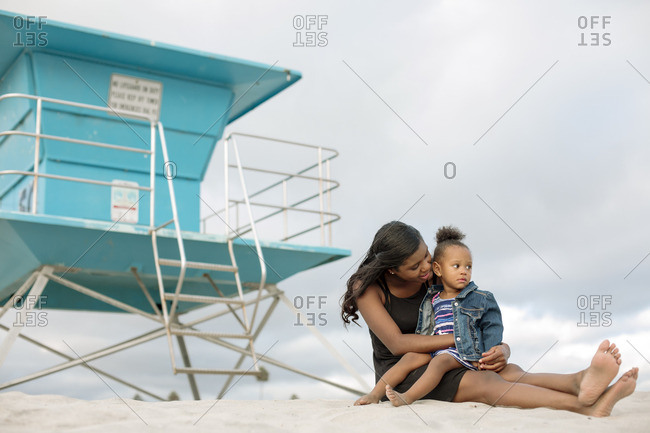 Mom sitting with her daughter on beach