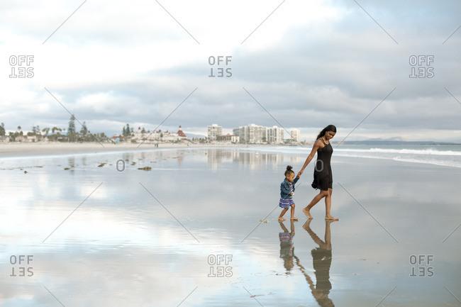 Woman and girl on ocean beach