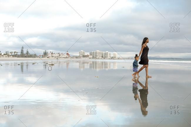 Woman and girl exploring ocean beach