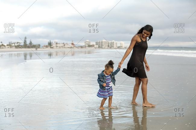 Woman and girl walking in ocean tide