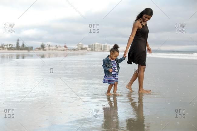 Woman and girl walking in sea tide
