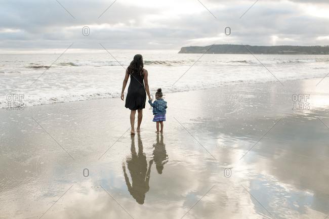 Woman and girl walking towards ocean