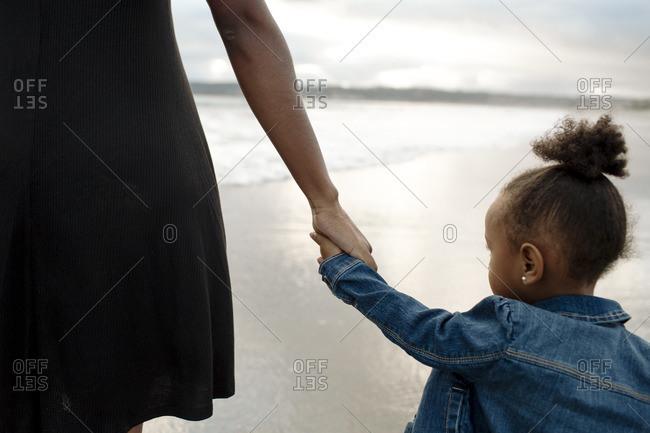 Girl holding woman's hand near ocean