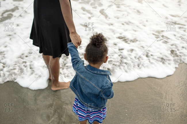 Girl standing by ocean holding woman's hand