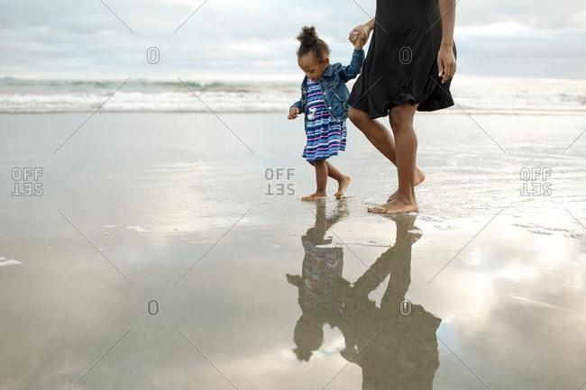 Girl walking along shore with woman