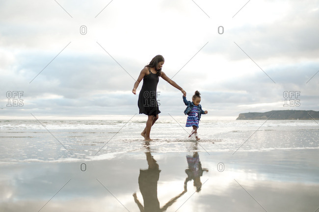 Girl jumping in tide with woman