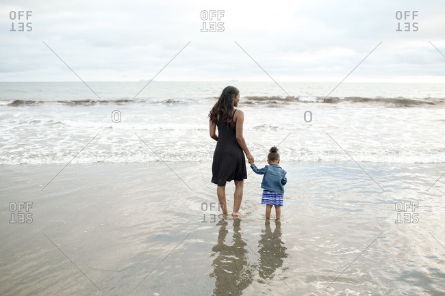 Girl and mom standing in tidal surf