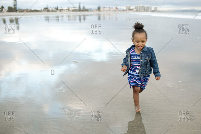 Barefoot smiling girl on a beach