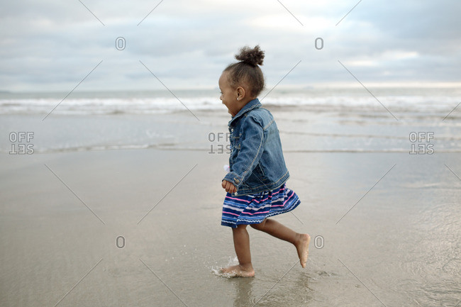 Barefoot girl laughing on a beach
