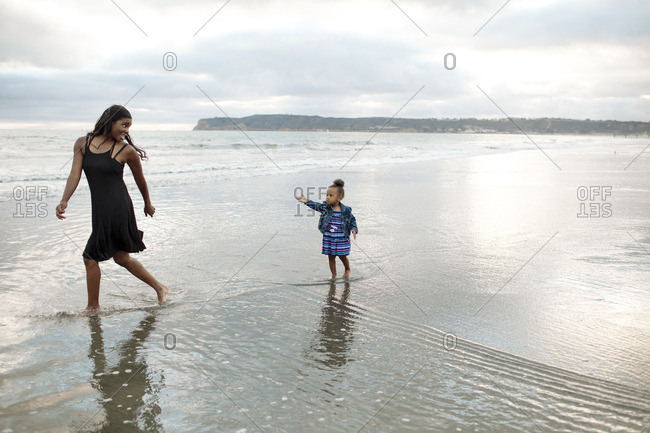 Mom playfully running from girl on beach