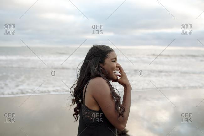 Black woman smiling joyfully on beach
