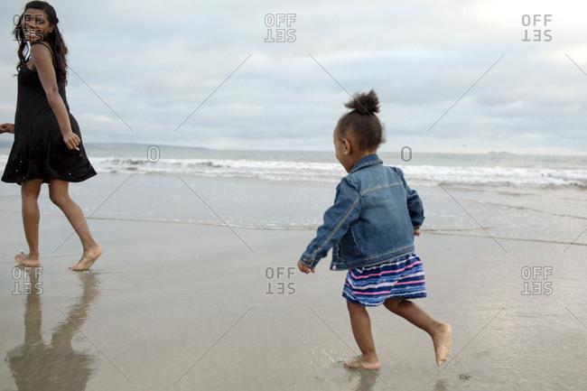 Girl running to mom on beach
