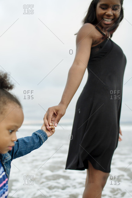 Woman holding on to girl's hand on beach