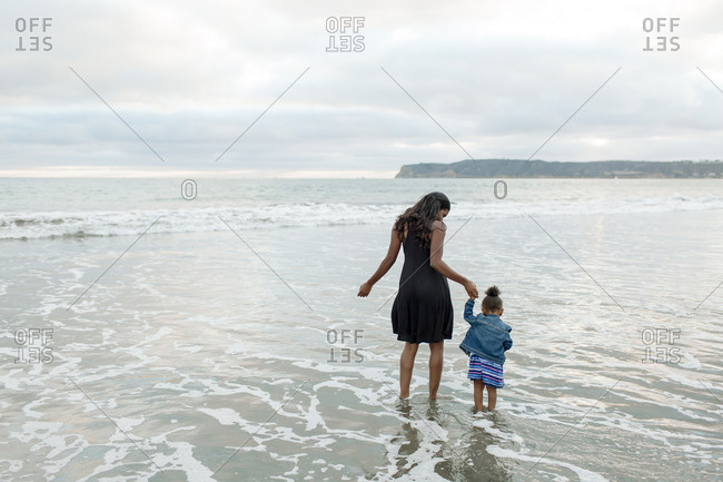 Mom and girl in tidal surf