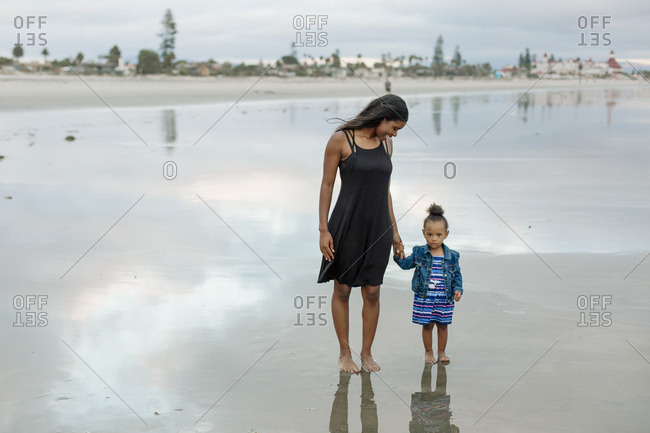 Woman and girl standing on ocean beach