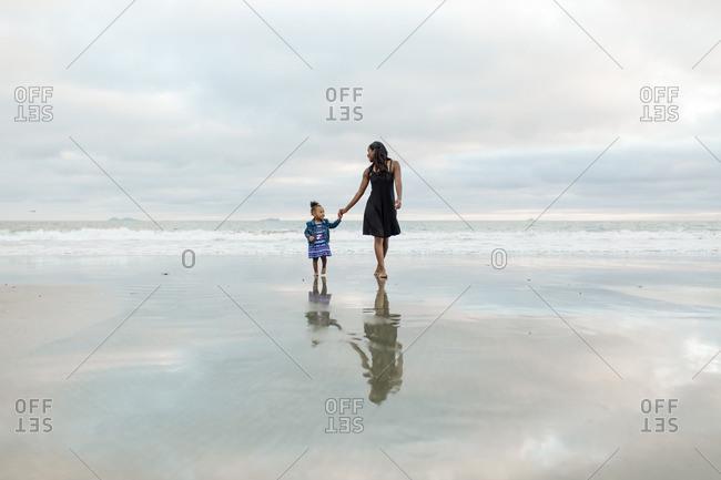 Woman and girl walking a coastline