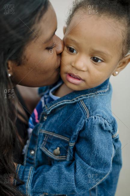 Woman kissing little girl by ocean