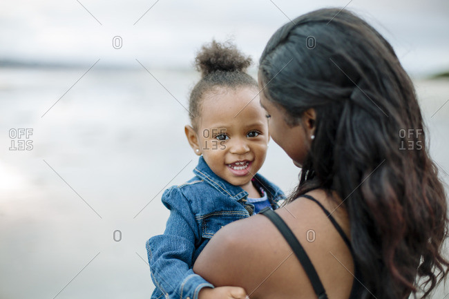 Happy girl in mom's arms on beach