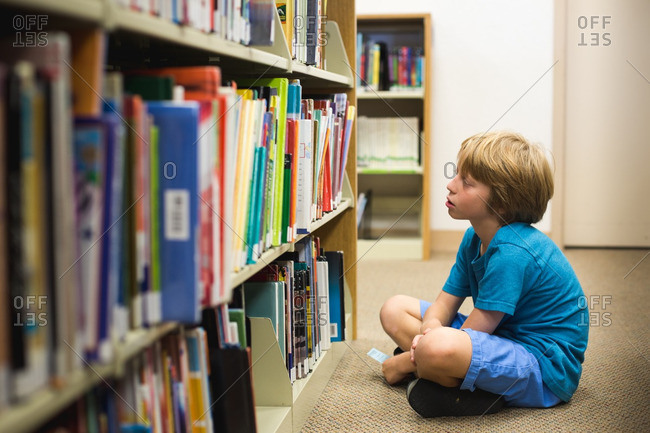 Child looking at bookshelf in school library