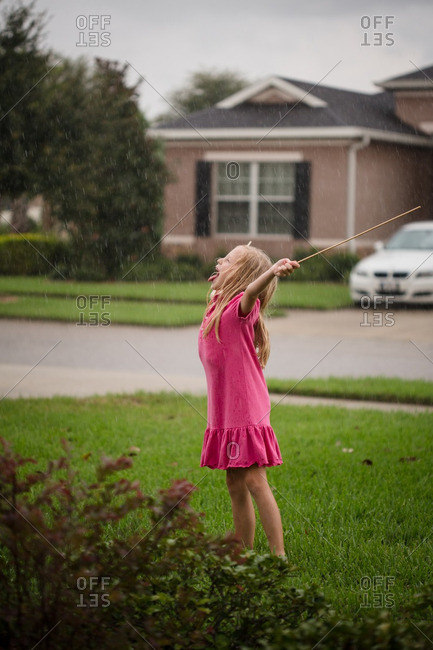 Girl catching raindrops on her tongue