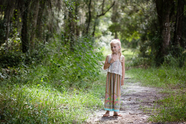 Little blonde girl walking on a trail in the woods