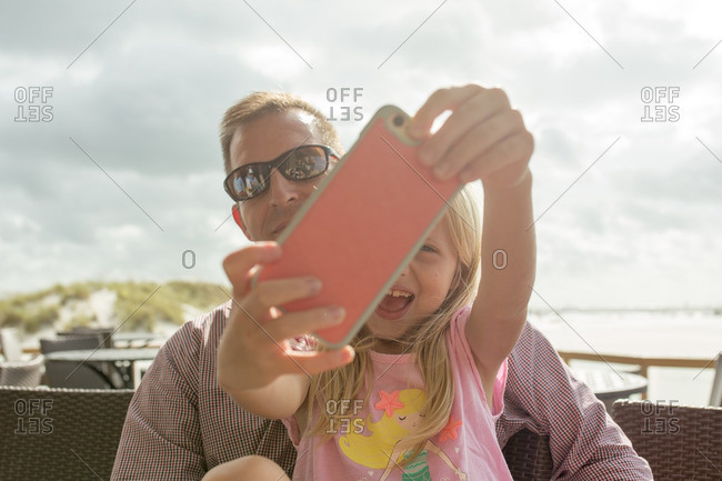 Little girl taking a selfie with her father