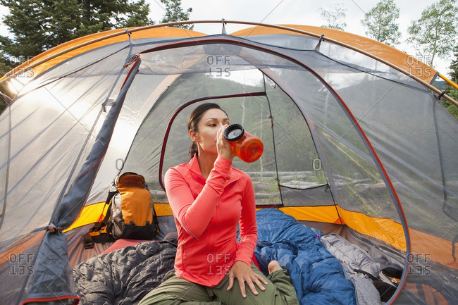 ... Mixed race woman drinking in tent & bivouac stock photos - OFFSET