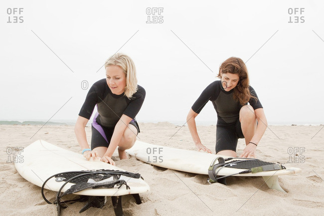 Caucasian women preparing to go surfing