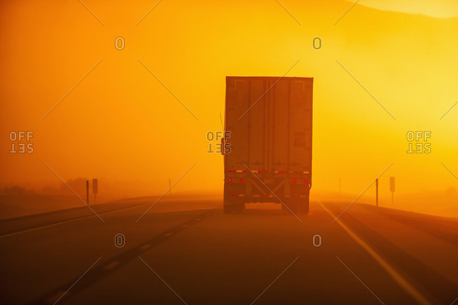 Truck driving down road in dust storm